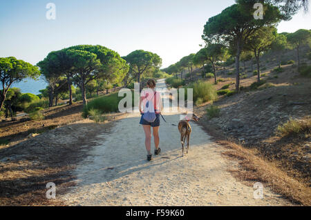 Woman with Spanish greyhound hiking the path between Barbate and Caños de Meca through the stone pine forest (Pinus - Stock Photo