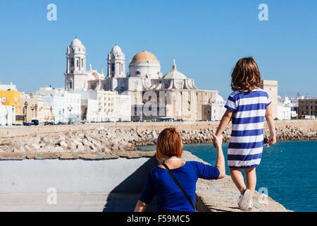 Tourists mother and daughter with blue striped t shirt on the promenade with the Cathedral of Cadiz, Andalusia, - Stock Photo