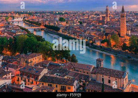 Santa Anastasia church and Torre dei Lamberti at dusk along the Adige river in Verona, Italy. - Stock Photo