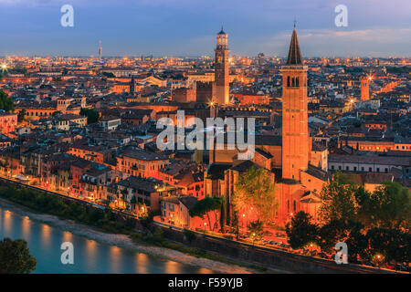 Santa Anastasia church and Torre dei Lamberti at dusk along the Adige river in Verona, Italy. - Stock Photo