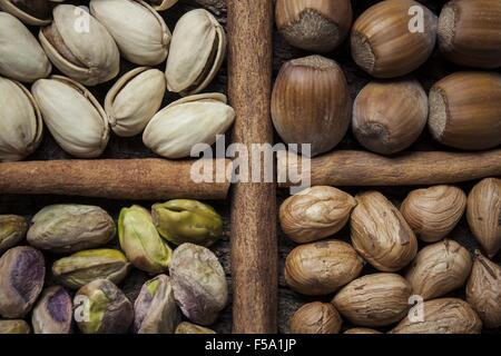 Composition with nuts, hazelnuts and pistachios close up on a cork bark - Stock Photo