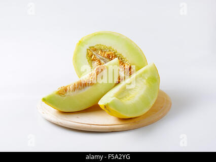 Yellow melon half and slices on cutting board - Stock Photo