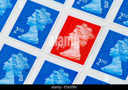 A first 1st class Royal Mail stamp among second 2nd class stamps - Stock Photo