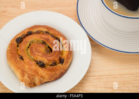 Pain au raisin pastry and a black coffee breakfast - Stock Photo