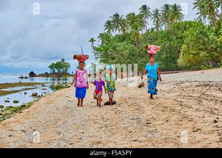 Woman walking along beach thoroughfare carrying burden on their heads - Stock Photo