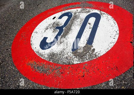 Road sign speed limit of thirty per hour - Stock Photo