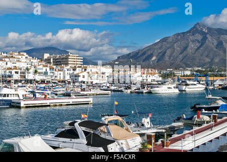 PUERTO BANUS ANDALUCIA SPAIN HARBOUR AND BOATS WITH MOUNTAINS AND CLOUDS - Stock Photo