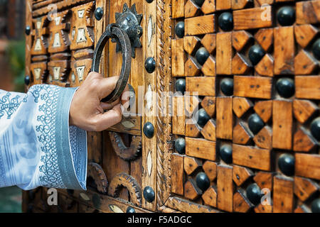 A hand holding a door handle of a traditional, wooden, Moroccan door, in South Morocco. - Stock Photo
