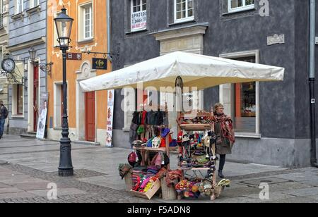 Gdansk, Poland 31st, Oct. 2015 Lady sales warm hand made hats and scarfs at Dluga street. Few tourists decided to - Stock Photo