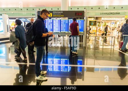 Barcelona, Spain, Airport 'El Prat', Terminal 1, Scenes, Man Looking at Smart Phone in Hallway, Departures Sign, - Stock Photo