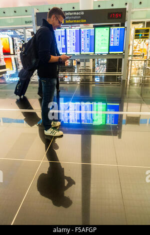 Barcelona, Spain, Airport 'El Prat', Terminal 1, Scenes, Man Looking at Smart Phone in Hallway, Departures Sign, - Stock Photo