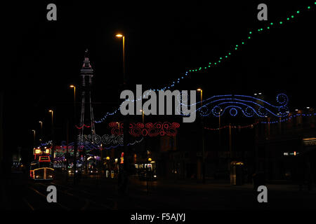 Night oblique view, to white lights Blackpool Tower, Scrolls Illuminations, Central Promenade by illuminated tram, - Stock Photo