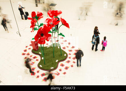 People swirling past a giant poppy installation on the concourse of Waterloo Station as part of London Poppy Day - Stock Photo