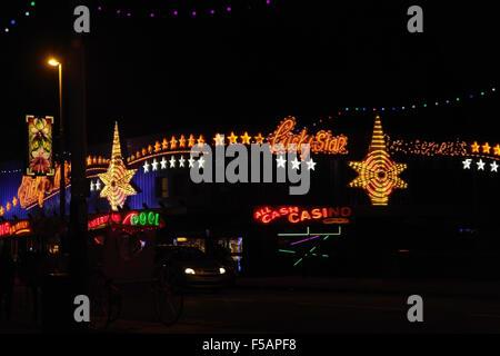 Night view across Central Promenade towards multi-coloured Lucky Star Amusement Arcade, Blackpool Illuminations, - Stock Photo