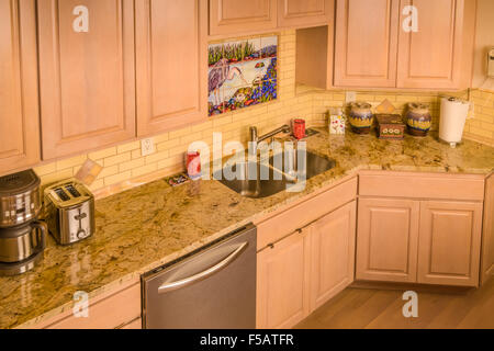 Remodeled kitchen with granite countertop and tile backsplash - Stock Photo