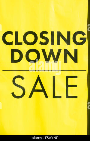 Death of the High Street metaphor / concept. Yellow closing down sign in shop window. Metaphor high street recession, - Stock Photo