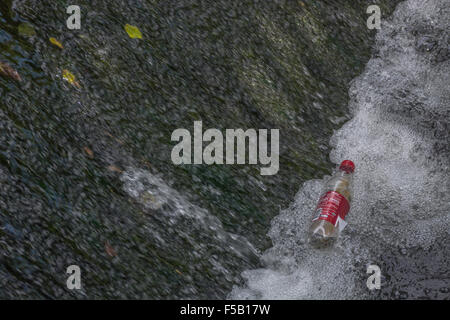 Empty soft drinks bottle caught in a cascading weir flow. Plastic waste, war on plastic concept. Metaphor environmental - Stock Photo
