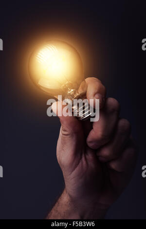 Creative energy and power of new ideas, innovation and creativity with hand holding light bulb, retro toned image
