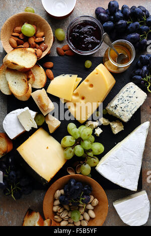 various cheeses and grapes on slate - Stock Photo