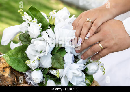 white bouquet on a rock and grooms hands one over the other with their wedding rings since - Stock Photo