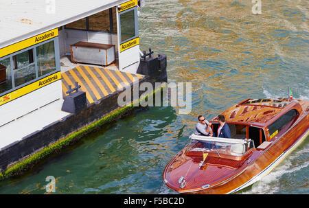 Motoscafi (water taxi) passes the Accademia vaporetto stop on the Grand Canal Venice Veneto Italy Europe - Stock Photo