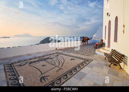 People sitting on a bench in Plaka village on Milos island, Greece - Stock Photo