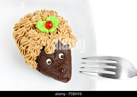 Chocolate cake decorated as hedgehog on white dish isolated - Stock Photo