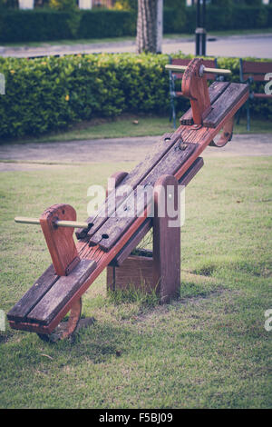 Old wood seesaw in childhood illustrating nostalgic concept. - Stock Photo