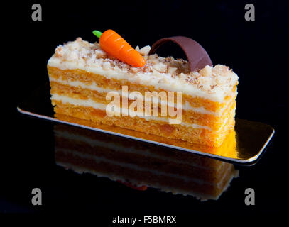 Side view of a homemade carrot cake with mascarpone cream cheese icing and handmade mini marzipan carrot decorations - Stock Photo