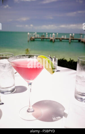 Latitudes Restaurant on Sunset Key, Key West, Florida, USA - Cosmopolitan drink with lime with boat dock in background. - Stock Photo