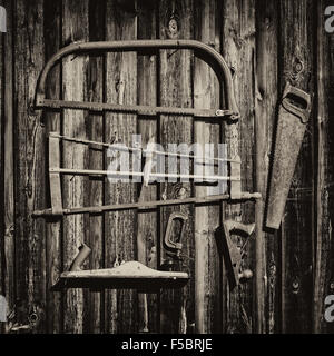 Carpenter tools on a wooden wall of an old barn - Stock Photo