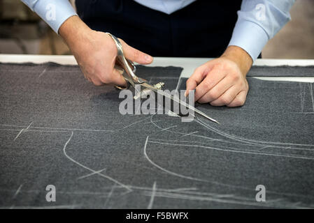 Tailor cutting fabric using large scissors or shears - Stock Photo