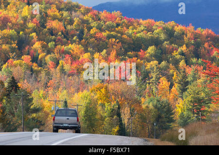 A car driving along the Kancamagus Highway, route 112, in New England in autumn, with colourful foliage, White Mountains New Hampshire USA