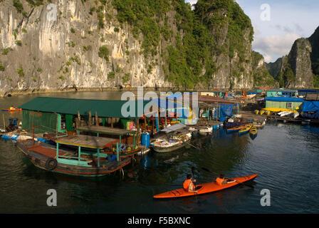 Kayaking past a floating fishing village in Halong Bay. Fish farm village amongst karst limestone mountains at Cat - Stock Photo