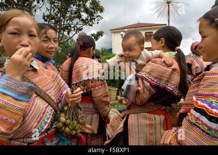 Bac Ha market. Flower Hmong people in traditional dress at weekly market, Sapa, Vietnam. Young women from the Flower - Stock Photo