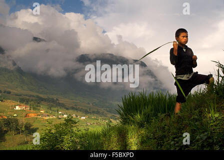 A child playing next to the rice terraces nearby of Lao Chai village. Trekking Sapa to Lao Chai. Vietnam. - Stock Photo