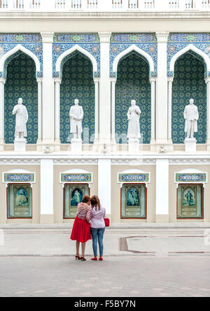 Two women standing in front of the Nizami Museum of Azerbaijan Literature in Baku. - Stock Photo