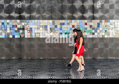 Two women walking past a tiled mural on Nizami street in Baku, the capital of Azerbaijan. - Stock Photo