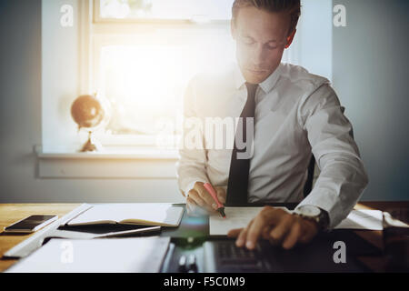 Executive business man working on accounts while being concentrated and serious, wearing white shirt and tie - Stock Photo