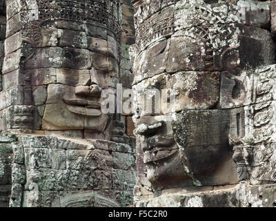 View of two of the many carved stone faces at the Angkor Thom temple complex in Cambodia - Stock Photo
