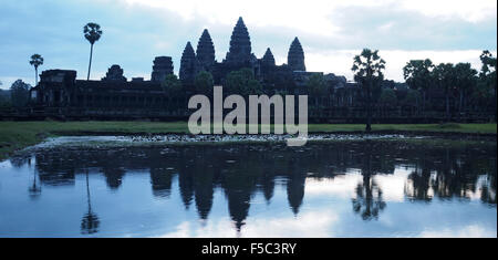 Beautiful view of the Angkor Wat temple in Cambodia silhouetted against the early morning sunrise - Stock Photo