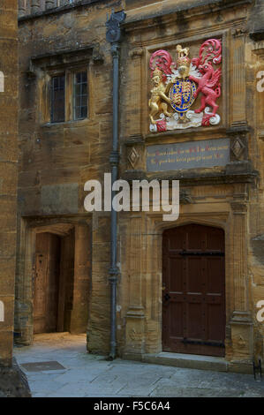 A small secluded courtyard in Sherborne School. Above a doorway is the Royal Coat of Arms of King Edward 6th. Dorset, - Stock Photo