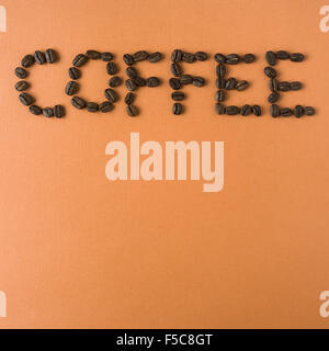 coffee spelled out with roasted coffee beans, on orange background - Stock Photo