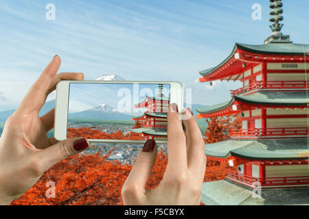 Back view of a woman taking photograph with a smart phone camera at Mt. Fuji with fall colors in Japan. - Stock Photo