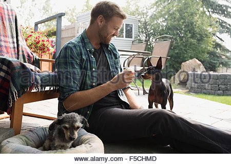 Man holding tennis ball for dog on patio - Stock Photo