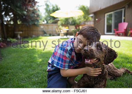 Affectionate boy hugging dog on lawn - Stock Photo