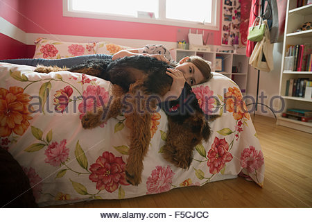 Girl hugging dog hanging off bed - Stock Photo