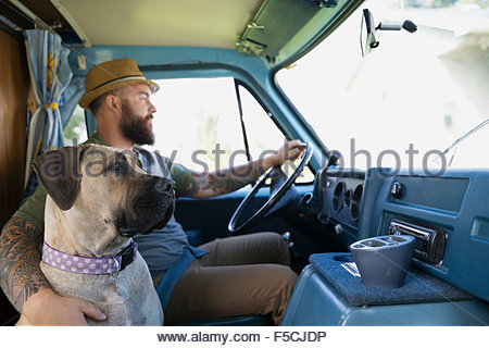 Dog riding with man in van - Stock Photo