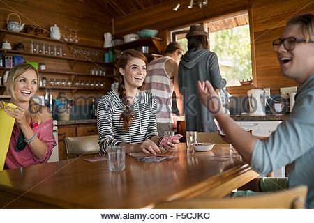 Young friends playing cards at cabin kitchen table - Stock Photo