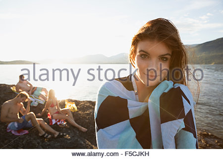 Portrait smiling young woman wrapped in towel lakeside - Stock Photo